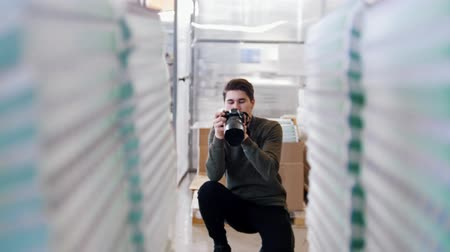 nakladatelství : Young male professional photographer shooting in front of paper stacks