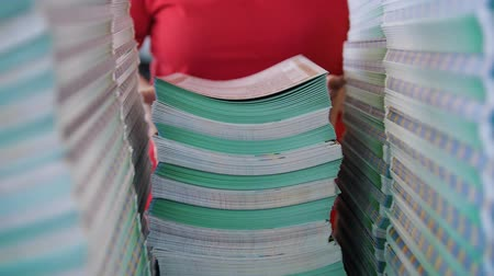 nakladatelství : Female worker lays out a large stacks of paper from the box in the typography