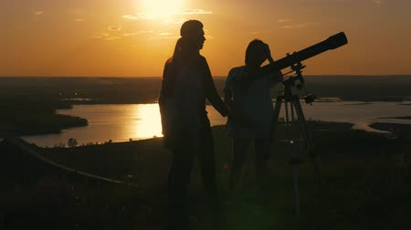 looking towards : Young happy friends looks through per view telescope and having fun at summer sunset