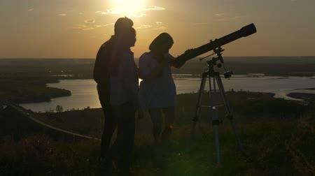 távcső : Young man showing friends beautiful view through telescope at summer sunset Stock mozgókép