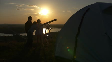 looking towards : Tourist tent in front of young friends looking beautiful view through telescope at summer sunset Stock Footage