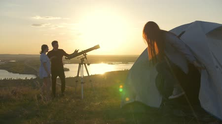 looking towards : Girl goes out from tent to friends to looking through telescope at summer sunset