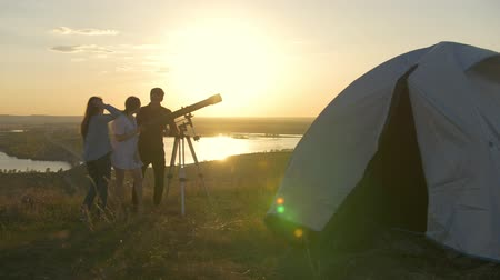 sátor : Young couple calling their friend to looking through telescope at sunset on the hill
