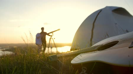 looking towards : Guitar on grass in front of young couple watching through telescope outdoors at sunset