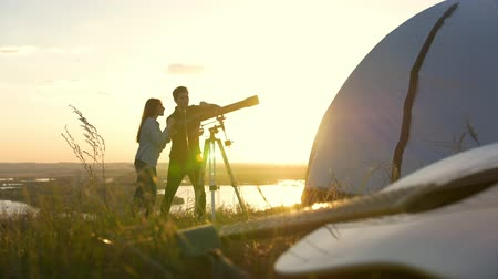 looking towards : Young friends watches through telescope on the hill at summer sunset Stock Footage
