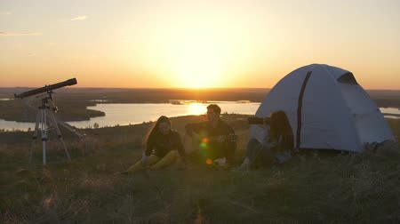 chill out : Young friends sitting near the tent singing songs with guitar at sunset