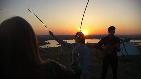 chill out : Young women dance with sparklers behind them guy playing guitar on the hill at sunset