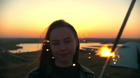 chill out : Portrait of young woman with sparkler stands on a hill at summer sunset Stock Footage