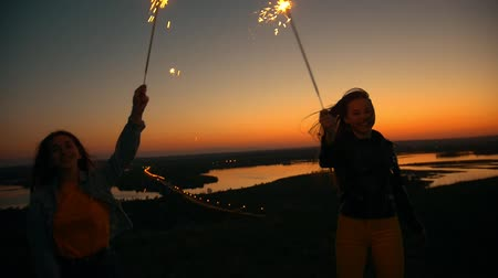 horizont : Two happy young women dancing with sparklers on a hill at summer sunset Stock mozgókép