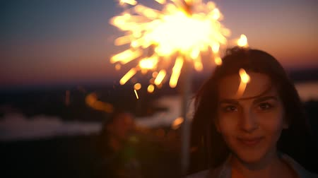 chill out : Smiling young woman looking at camera holding sparkler at summer sunset