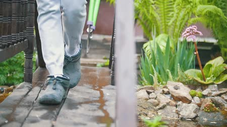 gumboots : Legs gardener goes with clippers in his hands on the bridge