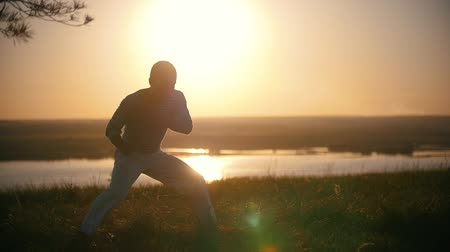 posando : The fighter makes kicks of legs in a turn on the background of the setting sun, slow-motion