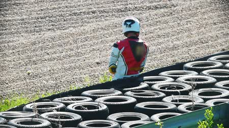 autobike : Motorcyclist resting near a pile of tires