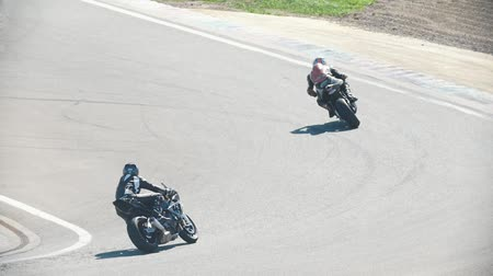 bikers : Two motorcyclists in the race, turn to the left, slow-motion Stock Footage