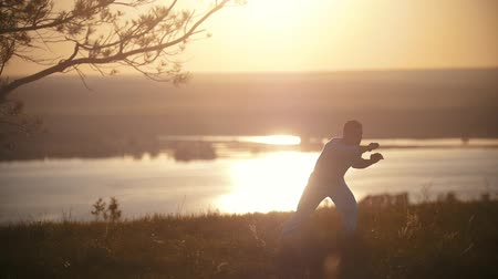 coaching : Fighter man training, orange sunset, slow-motion Stock Footage