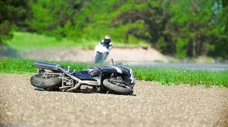 autobike : The motorcycle lies on the roadside, in the background the driver rides, slow-motion Stock Footage
