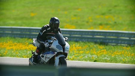 autobike : Motorsport - a motorcyclist on a red sportbike is driving along the strip, slow-motion Stock Footage