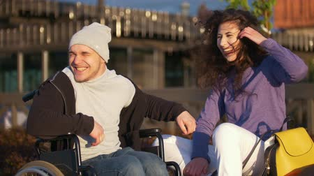 chlapík : Happy couple - disabled young man in a wheelchair with young woman enjoying the sunset together