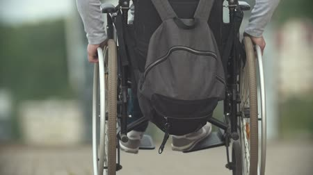 cadeira : Disabled man in a wheelchair riding at the city street Stock Footage