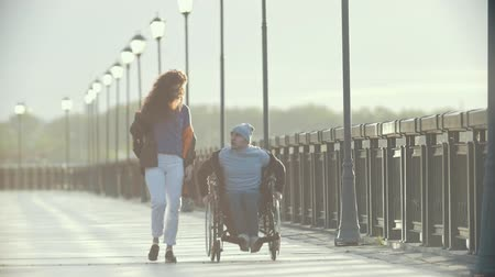 chlapík : Disabled man in a wheelchair walking together her girlfriend on the quay