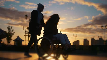 sosyal konular : Caring man with a disabled woman in wheelchair walking through the quay at sunset