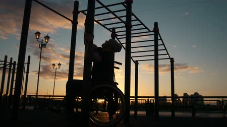 cadeira : Silhouette of disabled young man pulled up on the crossbars at the sunset outdoors