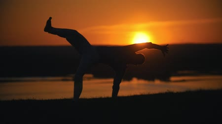 akrobatikus : Acrobatic man performing flips on the hill at summer evening sunset