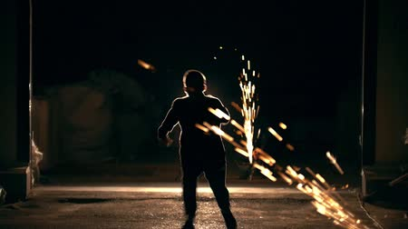 çevik : Young man run away through the sparks from grinder at night