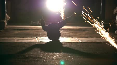 çevik : Silhouette of man performing acrobatic elements through the sparks from grinder Stok Video