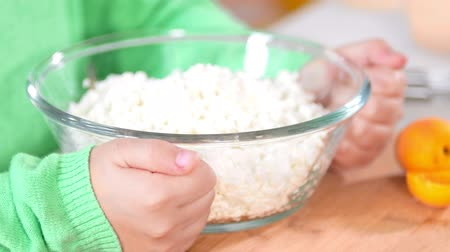 tvaroh : Hands of little girl with glass bowl of cottage cheese on the table