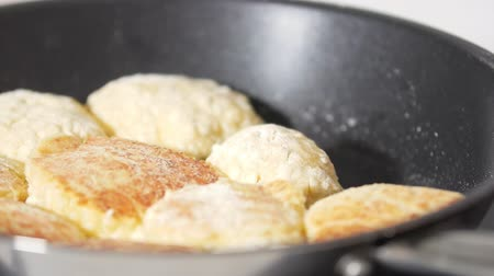 оладья : Female hand fries pancakes from cottage cheese in frying pan