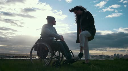 chlapík : Care of disabled - man in a wheelchair with woman talking at the cloudy sunset