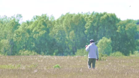 бункер : Man walking around with a golf stick on his shoulder on the summer field