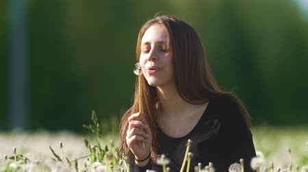 pampeliška : Cute happy girl blowing dandelion in a meadow of dandelions