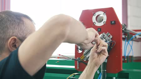 cabling : Electrician works with energy panel and machinery equipment on plant Stock Footage