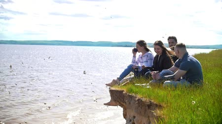 подростковый возраст : Cheerful friends sitting on the hill enjoying weekend in nature on the background of the river