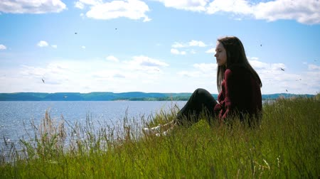 меланхолия : Thoughtful young woman sitting on the hill looking at the river in sunny day Стоковые видеозаписи