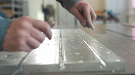 scraper : Male hands chamfering removing burrs on metal detail for manufacturing cnc machinery with a scraper