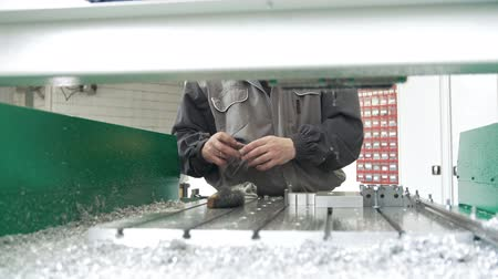 scraper : Worker with a scraper chamfering removing burrs on metal object for manufacturing industrial CNC machines