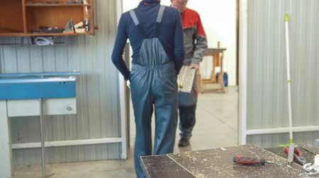 gyártó : Two men workers carries a metal panel at manufacturing CNC machinery