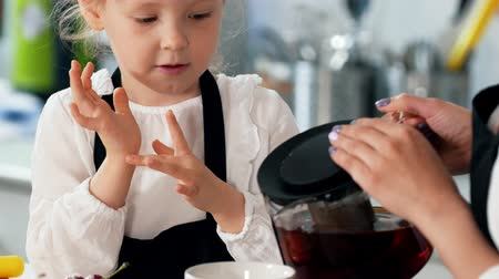 słodycze : Caring mother pours tea for her little daughter with homemade sweets Wideo