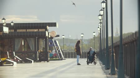 chlapík : Disabled man in a wheelchair talking on the phone walking together her girlfriend on the quay