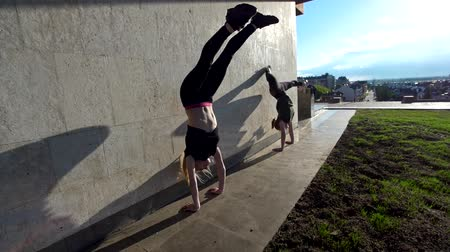 sznurek : Two female acrobat performs handstand on the wall at sunset outdoors