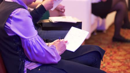 from behind : Female hands writes in a notebook at a conference Stock Footage