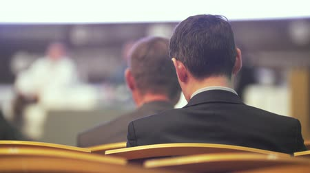 delegate : Rear view of young man sitting at the business conference Stock Footage