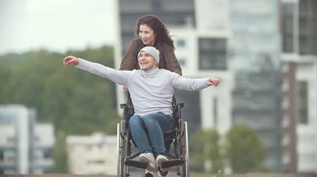 chlapík : Happy disabled man in a wheelchair with happy young woman running at the city street Dostupné videozáznamy