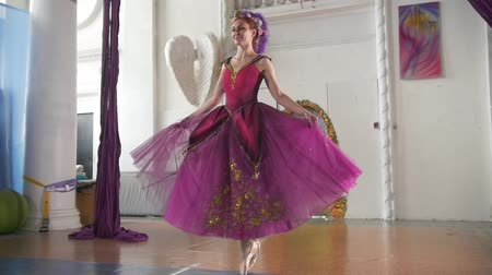 тапки : Young beautiful ballerina in purple dress performs dance in spacious white studio