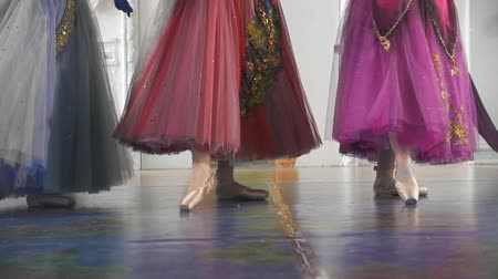 тапки : Three attractive ballerinas in colourful dresses dancing on pointe shoes in spacious studio Стоковые видеозаписи