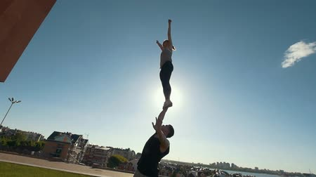 sznurek : Young couple practicing acrobatics performing front plank bird pose, young man raises flying young woman balancing on his arms at sunset Wideo