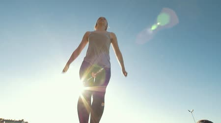 backflip : Young woman performs the twine in jump at the sunshine Stock Footage